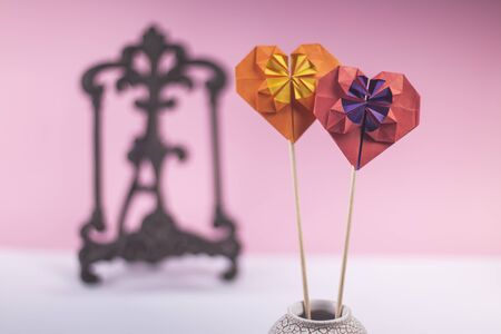 Concept of valentines day love handmade papercraft origami crafted colored paper heart close-up shot in studio