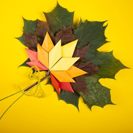 Fallen handmade leaves autumn concept traditional paper craft art origami topshot on yellow background
