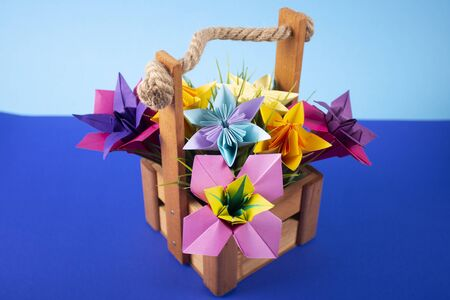 Handmade colored paper flowers origami bouquet paper craft art in a basket with grass in the studio on colored background