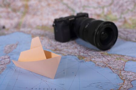 Travel holiday vacation concept camera and origami handmade papercraft paper ship on map near italy close up studion shot