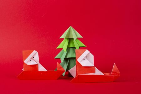Santa Claus on a sleigh with tree origami. Christmas concept winter crafted decorations studio shot