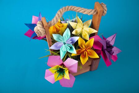 Handmade colored paper flowers origami bouquet paper craft art in a basket with grass in the studio on colored aqua background