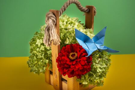 origami butterfly crafted on a green bush in a basket on a colored background beautiful bouquet studio close shot