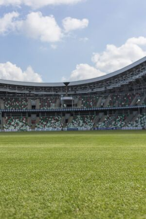 Interior view of the grass field and empty seating grandstands of stadium under summer clouded blue sky. Quarantine, waiting sport season concept Foto de archivo