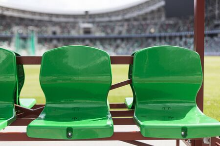 Coach and staff bench, green plastic seats at empty football stadium. canceled sports events concept Foto de archivo