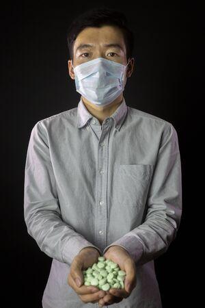 Man in medical mask, hands full of medications.