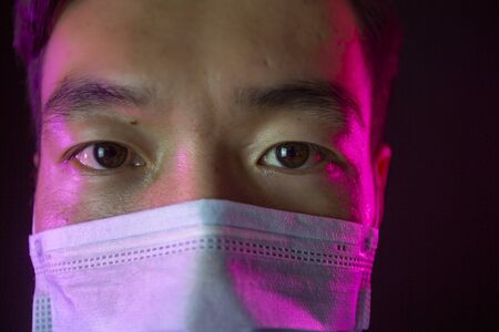 Close up portrait. Asian man in facial mask against 2019-nCov. Black background Stock fotó