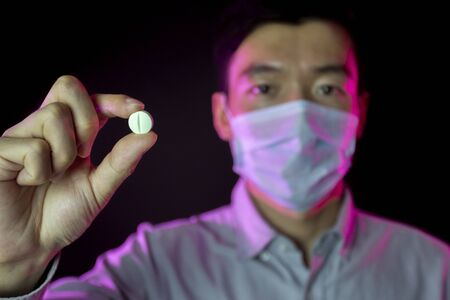 a guy in surgical mask. Focus on pill in hand.