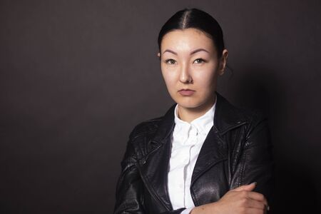 Serious asian woman looking directly at camera. Isolated on black background