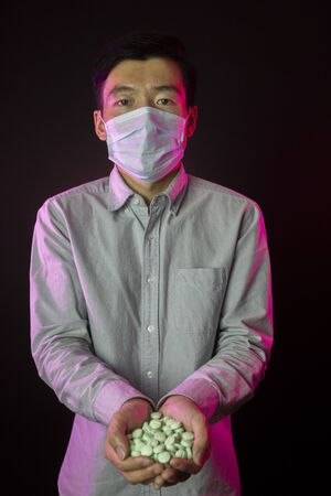 guy in medical mask with hands full of medications. Virus protection