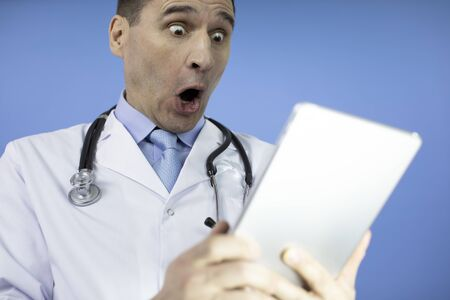 Portrait of shocked male doctor with stethoscope looking at laptop