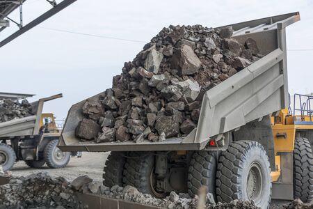 Mining industry: heavy dump trucks unload granite into huge rock crusher