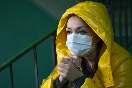 Caucasian girl in medical mask in abandoned building sits and looking away Stock Photo