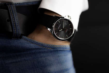 Saint-Imier, Switzerland 31.03.2020 - Closeup fashion image of Longines watch on wrist of man: mans hand in blue jeans pocket with white cuff of plaid shirt. Longines man watch stainless steel case Longines man watch stainless steel case black clock face  Editorial