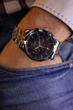 Ibach, Switzerland 31.03.2020 - Closeup fashion image of Victorinox watch on wrist of man: mans hand in blue jeans pocket with white cuff of plaid shirt. Victorinox man watch stainless steel case, black clock face dial stainless steel bracelet swiss quart Redactioneel