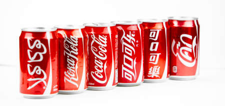 Atlanta, Georgia, USA April 4, 2020: several cans of Coca-Cola with a logo in different languages: Russian, Arabic, Korean, English, Thai . global brand globalism concept.