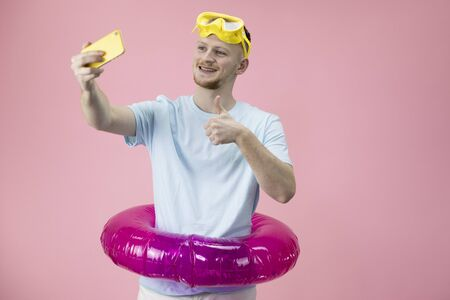 happy gesticulating young businessman in inflatable swim ring making selfies Banco de Imagens