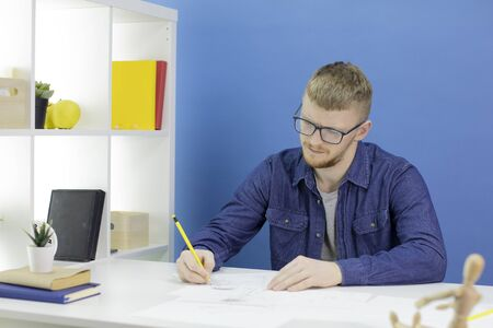 Thoughtful focused young designer draws with pencil in studio with wooden dummy