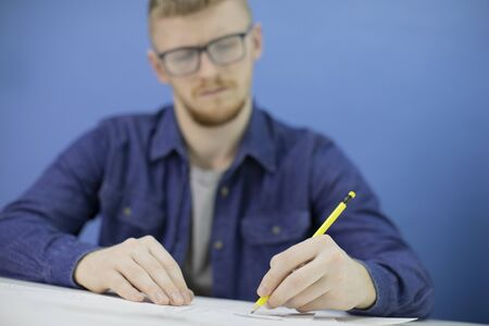 Thoughtful focused young designer draws with pencil isolated on blue background