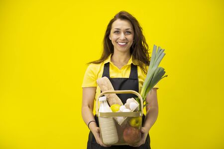 Portrait of happy farmer with basket of groceries and organic farm eco products