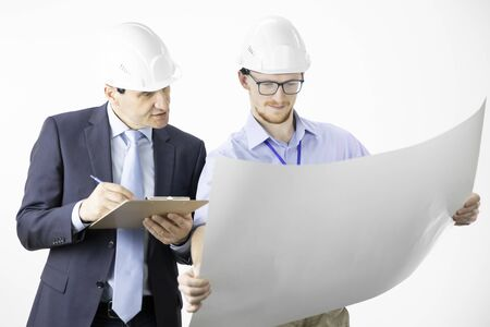 Architectural engineers working with blueprint documents marking edits 写真素材