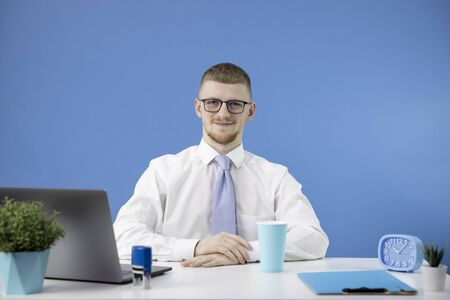 manager in office looks at camera with smile accent on blue color