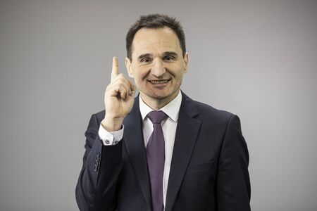 handsome 40s businessman smiling pointing up with his forefinger