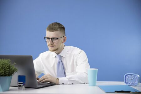male manager in office concentrates on laptop, accent on blue colour