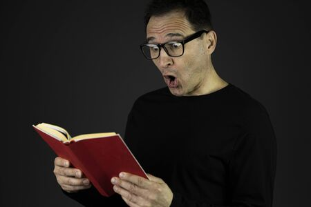 Surprised handsome man in casual black wear and glasses reading adventure book isolated on dark background. Scientific literature, surprise new knowledge, interesting facts, literature fans concept