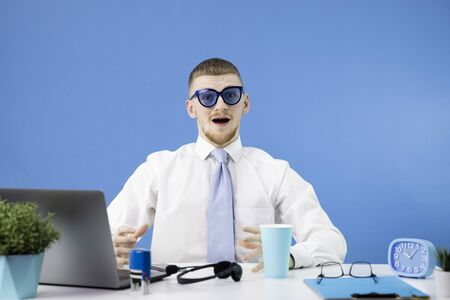 Young handsome Caucasian cheerful man dressed in a classic shirt with a blue tie looks in surprise at the camera and opens his mouth wide. Ludicrous funny blue sunglasses. Stylish office interior.