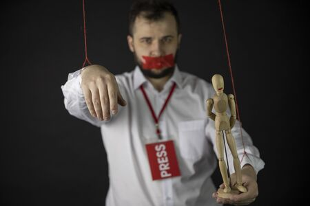 Man with badge press holds hands tied with ropes like marionette with wrapping mouth by adhesive tape and dummy in hand on dark background. Basic rights, journalism, freedom of Press, speech, media