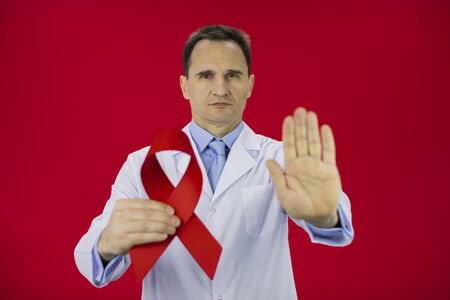 Handsome serious male senior age doctor in white lab coat with red ribbon in hand shows stop sign isolated on red background Symbol of HiV Aids struggle, awareness, medical sign, world aids day