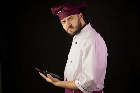 Confused chef man in uniform holds calculator suspiciously looks at camera. Ð¡ook in apron on black background. Restaurant bankruptcy, food industry crisis, business problems, incur loss, breakeven