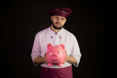 Sad chef man in uniform holds broken pink piggy bank with band-aid. Depressed cook in apron standing on black background. Restaurant bankruptcy, food industry crisis, business problem, liquidation