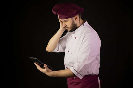 Shocked chef man in uniform holds calculator and looks on it with surprise. Ð¡ook in apron on black background. Restaurant bankruptcy, food industry crisis, business problem, liquidation, incur loss