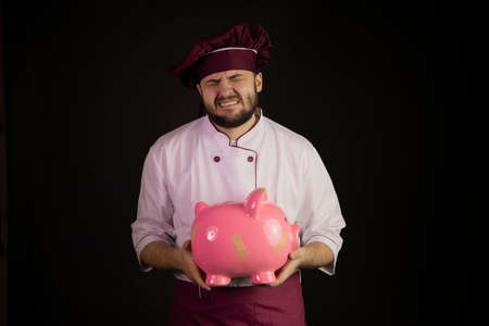 Crying chef man in uniform holds broken pink piggy bank. Sad male cook in apron standing on black background. Professional cooking master, restaurant bankruptcy, food industry crisis, business problem