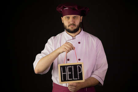 Sad chef man in uniform holds chalk board with inscription HELP. Depressed cook in apron on black background. Restaurant bankruptcy, food industry crisis, business problem, small business support