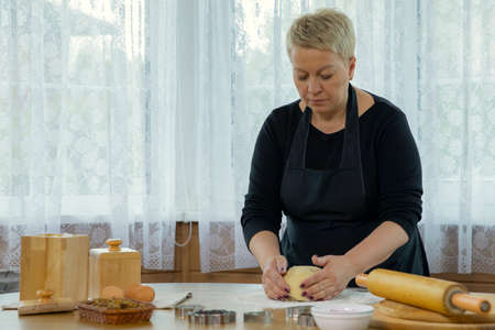 middle-aged woman wearing black apron mashing dough for preparing gluten-free rolls in kitchen �ookery class in country wooden house family traditions concept Homemade baking lesson concept