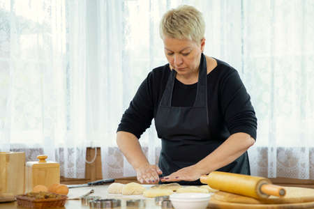 middle-aged woman in black apron making homemade cookies and pastry kneading dough in kitchen �ookery class in country house. family traditions concept Homemade baking lesson concept. blogging concept