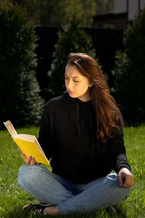 Attractive focused on brunette girl with long hair dressed in black hoodie sitting on green lawn reading yellow book on nice summer day. Relaxed vacation concept. Distance Education Concept Foto de archivo