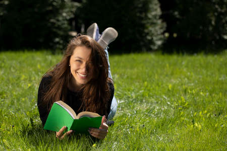 Attractive smiling brunette long hair girl dressed in black hoodie lying on grass of green lawn on nice summer day reading book looking at camera. Relaxed vacation concept Distance Education Concept