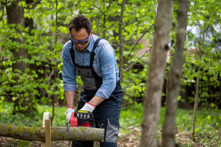 middle-aged man in overalls saws wood with chain saw using sawhorse. domestic work concept. Hand harvesting of firewood in forest. jack of all trades concept
