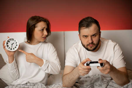 Young couple quarrel in bedroom due to gambling addiction. Handsome excited man with joysticks in hands playing video games in bed at night ignoring his wife, girl swears with him and points to clock Stock fotó