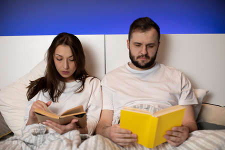 Beautiful young couple sitting in bed reading books at home in bedroom, smart girl and guy resting before bedtime, book lovers bibliophile match, book store advertisement, student, exciting reading Stock Photo