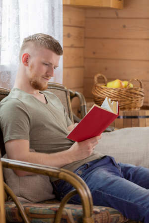 young man reading book with red cover on wicker bench in countryside wooden house against background of basket of yellow apples. indoors relaxation concept. Free time concept. concentration concept