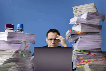 tired swamped with documents office worker using laptop computer and doing overtime project sitting at desk with huge pile of papers. Fatigue and overload concept. isolated on blue bureaucracy concept