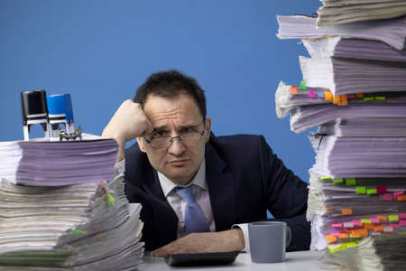 businessman in glass and tie sitting at office desk with huge stack of documents looking sad and depressed in business stress and crisis concept. Fatigue and overload concept. isolated on blue