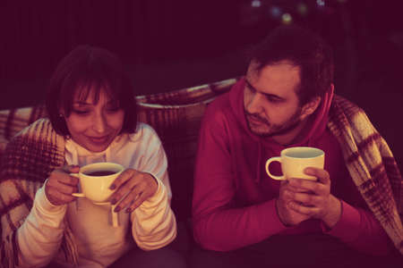 Happy romantic travelers resting at bonfire. The concept of active recreation and travel. couple of lovers drinking coffee or tea while they talk and cover themselves with blanket at romantic party.