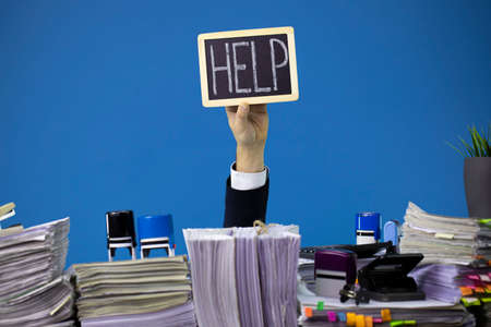 Hand of caucasian businessman emerging from office desk loaded of paperwork, invoices and lot of papers and documents asking for help holding cardboard overworked in giving up concept isolated on blue Banque d'images
