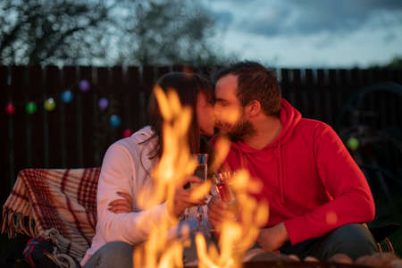 romantic party by bonfire, couple of lovers kissing with champagne glasses in their hands against background of fire. Portrait Of Lovely Happy Man And Beautiful Woman Near Camping In Nature